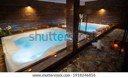 Private whirlpool in a wellness center. Indoor whirlpool with bubbles. Candles around a whirlpool with blue water.  Stock photo ©