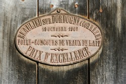 Prize medal from cattle competition hung on barn door in correze, france