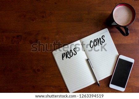 Pro and Contra concept. Smartphone, hot chocolate cup for drinking, pen and notebook written with text PROS and CONS on office wooden desk. Creative office table lay out view from top.