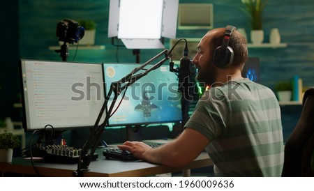 Pro cyber man streaming videogame, reading on stream chat and playing space shooter on RGB powerful computer. Streamer sitting on gaming chair playing game during online esports tournament.