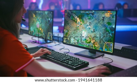 Pro Girl Plays Computer Game Plays RPG Strategy on a Championship. Diverse Esport Team of Pro Gamers Play in Mock-up Video Game. Stylish Neon Cyber Games Arena. Over The Shoulder Shot