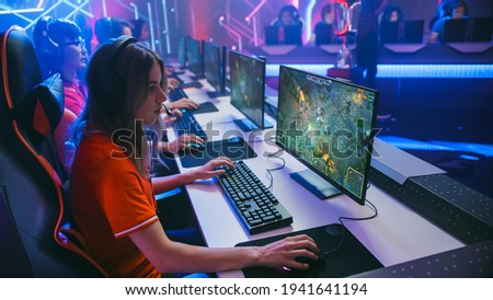Pro Girl Plays Computer Game Plays RPG Strategy on a Championship. Diverse Esport Team of Pro Gamers Play in Mock-up Video Game. Stylish Neon Cyber Games Arena. Side View Shot
