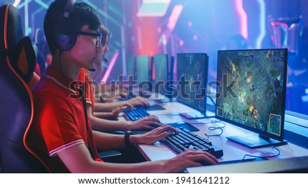 Pro Girl Plays Computer Game Plays RPG Strategy on a Championship. Diverse Esport Team of Pro Gamers Play in Mock-up Video Game. Stylish Neon Cyber Games Arena. Side View