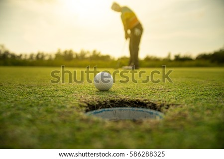 Pro Golf long putting golf ball in to the hole, sunset scene time.