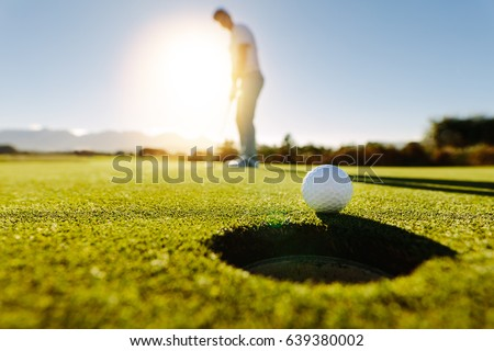 Shutterstock Pro golfer putting golf ball in to the hole. Golf ball by the hole with player in background on a sunny day.