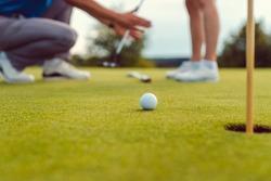 Pro on golf course teaching a woman how to put, close-up