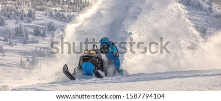 Pro snowmobiler makes a turn and lets a flurry of snow spray from under the caterpillar. sports snowmobile in the mountains. bright skidoo motorbike and suit without brands. Winter fun. panoramic view Stock photo ©