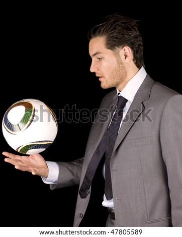 Pro soccer player juggling a ball wearing a business suit