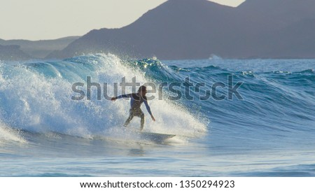 Pro surfboarder riding big barrel ocean waves in beautiful Fuerteventura. Cheerful young man in wetsuit skilfully carving breaking waves in the Canaries. Surfer catching waves on cool active holiday #1350294923