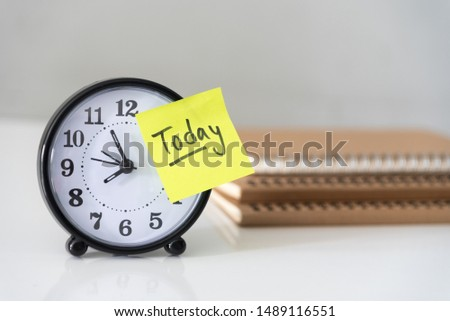 Proactive and beginning for action concept, handwriting word Today on yellow sticky paper over alarm clock and pile of books. #1489116551
