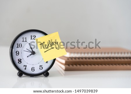 Proactive and beginning for action concept, handwriting word Today on yellow sticky paper over alarm clock and pile of books. #1497039839