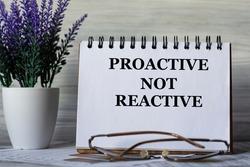 PROACTIVE NOT REACTIVE - words in a notebook on a light background with glasses and a bouquet of lavender. Business concept