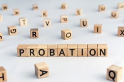 probation - word from wooden blocks with letters, period of time criminal is allowed to stay out of prison or period a new employee is suitable for work concept, random letters around