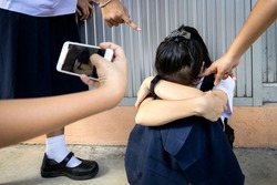 Problem of bullying at school,sad stressed asian girl student in Thai school uniform sitting on the floor with hands on knees,scared,anxious victim of bullying and video recorded on a mobile phone