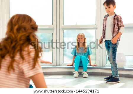 Problem with peers. Sad unhappy girl sitting near the window while having problems with her peers in the kindergarten #1445294171
