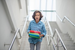Problems at school. Upset schoolboy walking downstairs, carrying books