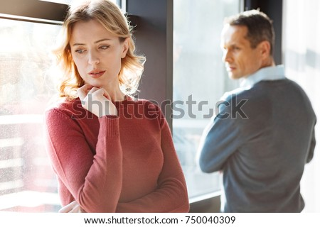 Problems in relationships. Sad unhappy cheerless woman standing near her boyfriend and holding her chin while feeling depressed