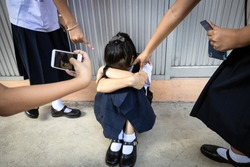 Problems of bullying at school,sad stressed asian girl student crying sitting on the floor,group of hands pointing finger to scared schoolgirl, bullying victim being video recorded on a mobile phone