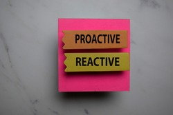Procative Vs Reactive write on sticky note isolated on Office Desk