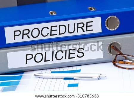 Procedure and Policies - two binders on desk in the office #310785638