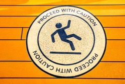 Proceed With Caution sign to alert of slippery floor showing symbol of person falling to the ground.