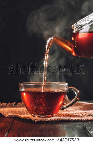 Process brewing tea,tea ceremony,Cup of freshly brewed black tea,warm soft light, darker background.