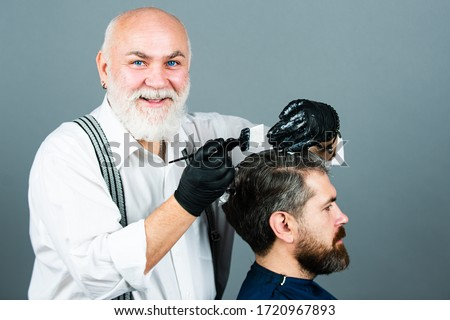 Process of a guy having his hair dyed at hairdresser. Hair coloring man agains grey hair. Professional senior hairdresser drying hair