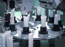 Process of automatic cosmetic tubes filling and sealing machine. Pharmaceutical industry