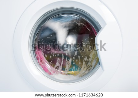Process of cleaning color cloth in washing machine, closeup, nobody