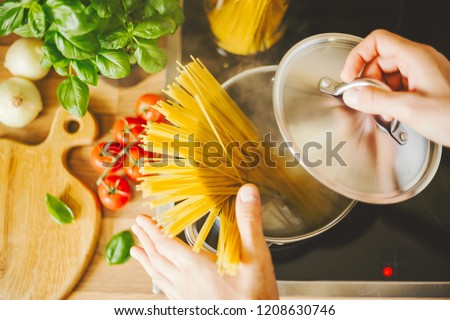 Process of cooking homemade italian pasta. Lifestyle background. Man droping spaghetti into boiling water. Closeup. Horizontal.