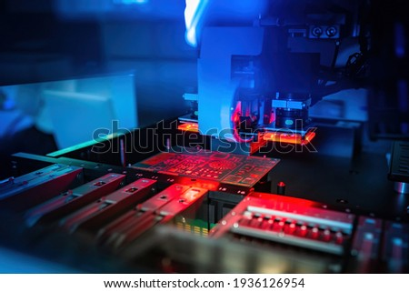 Process of creating a printed circuit board. Machine for production of PCB. Manufacturing of printed circuit boards. PCB board in a laser machine. Concept - testing printed circuit boards with laser