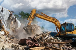 Process of demolition of old building dismantling. Excavator breaking house. Destruction of dilapidated housing for new development