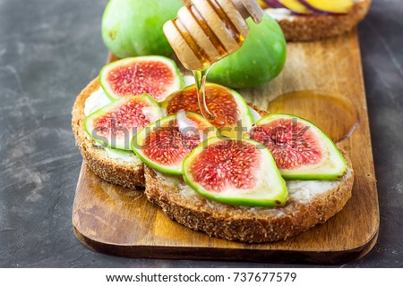 Process of Drizzling Honey with Wood Dipper on Wholegrain Bran Rye Toast with Cream Cheese or Ricotta and Fresh Ripe Figs. Cutting Board. Close Up