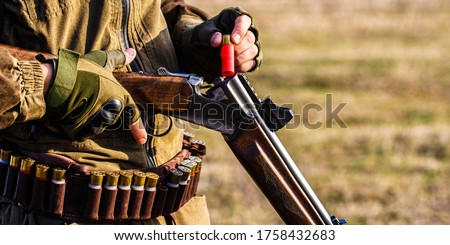Process of hunting during hunting season. Male hunter in ready to hunt. Closeup. Hunter man. Hunting period. Male with a gun, rifle. Man is charging a hunting rifle.