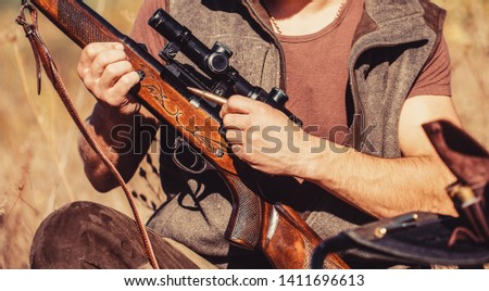 Process of hunting during hunting season. Male hunter in ready to hunt. The man is on the hunt, sport. Hunter man. Hunting period. Male with a gun, rifle. Man is charging a hunting rifle. Close up.