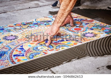 process of laying floor ceramic tiles, installation of tiles on the glue #1046862613