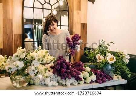 Process of making a bouquet of seasonal flowers. Female florist making bouquet in flower shop. Photo stock ©