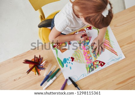 Process of making art. Cute little girl in art school draws her first paintings by pencils and markers. #1298115361