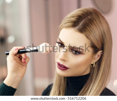 Process of making makeup. Make-up artist working with brush on model face. Portrait of young blonde woman in beauty saloon interior. Applying tone to skin. #556712206