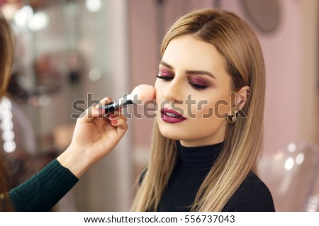 Process of making makeup. Make-up artist working with brush on model face. Portrait of young blonde woman in beauty saloon interior. Applying tone to skin. #556737043