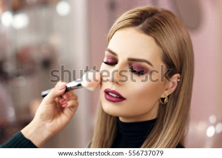 Process of making makeup. Make-up artist working with brush on model face. Portrait of young blonde woman in beauty saloon interior. Applying tone to skin.