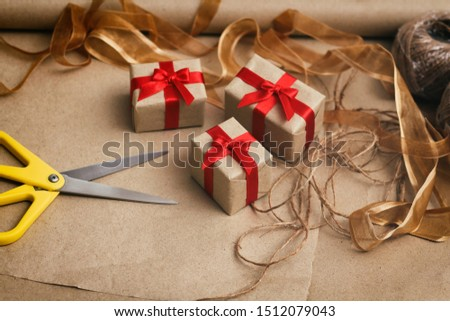Process of packing presents in gift boxes. Craft paper, scissors, hemp threads, red satin ribbon.
