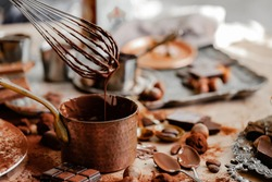 Process of preparation of delicious homemade dark chocolate. Whisk mixer, vintage tableware, ingredients on the table. Gourmet dessert. Close up, macro