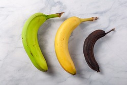 Process of ripening for banana showing a fresh green to yellow banana on left, an optimal ripened yellow banana in middle and a stale banana that turned dark brown due to enzymatic browning on right