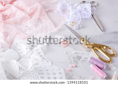 Process of sewing elegent lingerie.Sewing process, golden and silver scissors, pins, spools of thread and pins