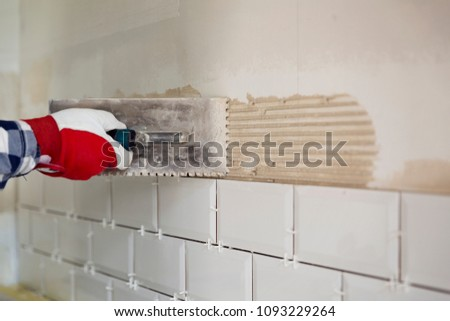 Process of tiling the tiles in the kitchen. Home improvement, renovation concept #1093229264