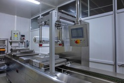 Processing of Packaging of butter and Cheese on food vacuum packaging sealing machine in food industrial factory. Packing food butter and Cheese in production line. Vacuum machine.