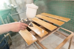Processing of wooden boards with varnish. Man spraying varnish on the parquet