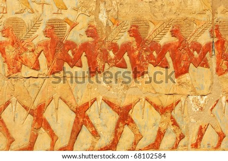 procession of Egyptians carrying axes and branches in the hathor chapel of the new kingdom mortuary temple of Queen Hatshepsut at Thebes in Egypt
