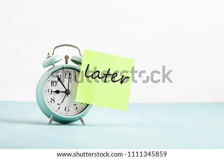 Procrastination, delay and urgency concept. Bad time management. Word later sticked to alarm clock